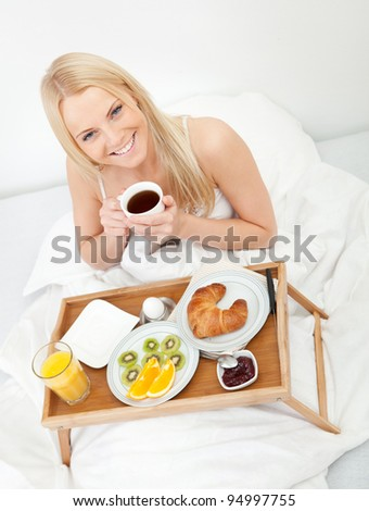Beautiful woman drinking coffee in bed - stock photo