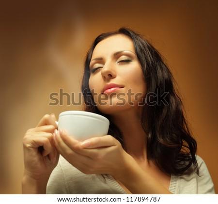 Beautiful woman drinking coffee or tea - stock photo