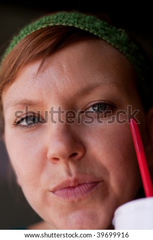 Beautiful woman drinking from a red straw - stock photo