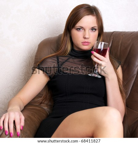 Beautiful woman drinking red wine sitting on a leather sofa - stock photo