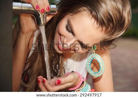 Beautiful woman drinking tap water outside - stock photo