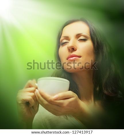 Beautiful woman drinking tea on green blurred background - stock photo