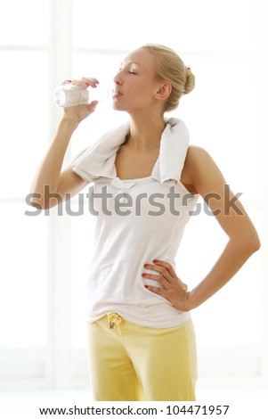 Beautiful woman drinking water after fitness workout - stock photo