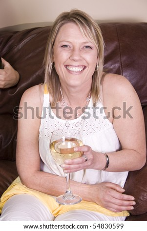 Beautiful Woman Drinking Wine at Home on the Couch - stock photo