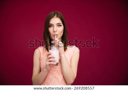 Beautiful woman drinking yogurt over pink background. Looking at camera  - stock photo