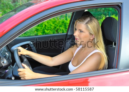 beautiful woman driver in red shiny car outdoors smiling - stock photo