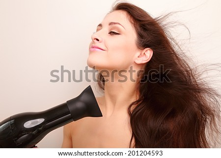 Beautiful woman drying long healthy hair with natural joying emotion - stock photo