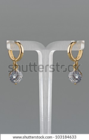 Beautiful woman earrings with diamonds on gray background - stock photo