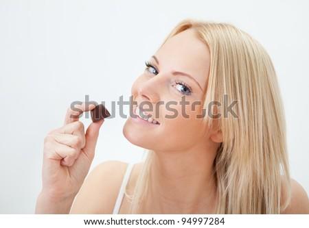 Beautiful woman eating chocolate - stock photo