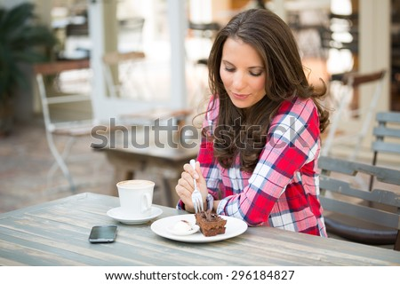 Beautiful woman eating chocolate cake at cafe - stock photo