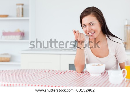 Beautiful woman eating her breakfast in her kitchen - stock photo