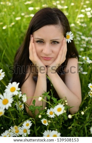 Beautiful woman enjoying daisy field, nice female lying down in the meadow of flowers, pretty girl relaxing outdoor, having fun, happy young lady and spring green nature, harmony and freedom concept - stock photo