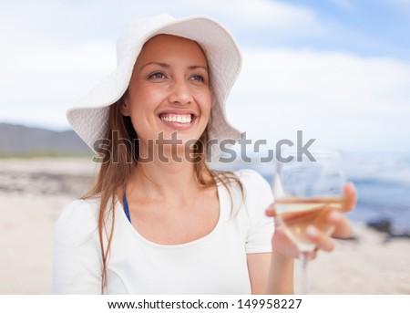 Beautiful woman enjoying glass of wine by the sea - stock photo