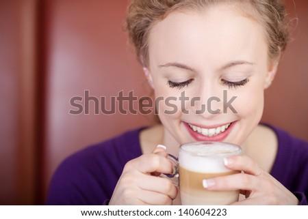 beautiful woman enjoying latte macchiato at coffee house - stock photo