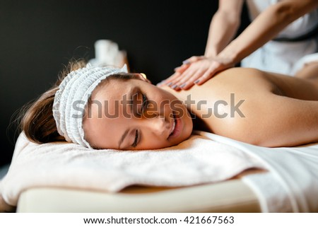 Beautiful woman enjoying massage treatment given by therapist - stock photo