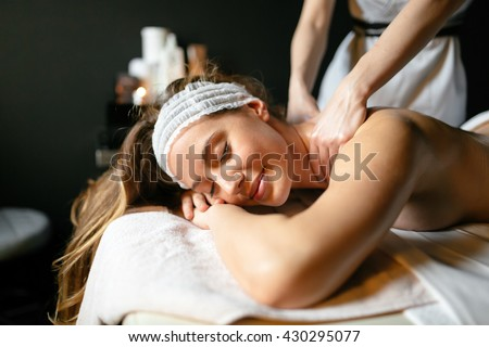 Beautiful woman enjoying massage treatment given by therapist - stock photo