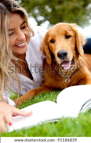 Beautiful woman enjoying with her dog outdoors - stock photo
