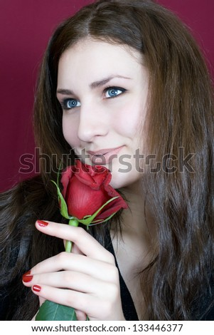 Beautiful woman enjoys the scent of red roses - stock photo
