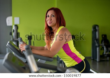 Beautiful woman exercising on an exercise bike - stock photo