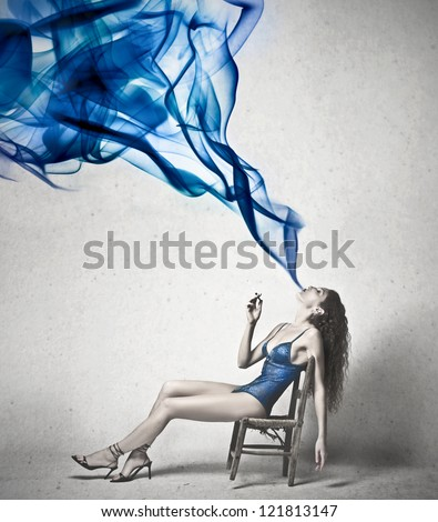 Beautiful woman exhales a blue smoke - stock photo
