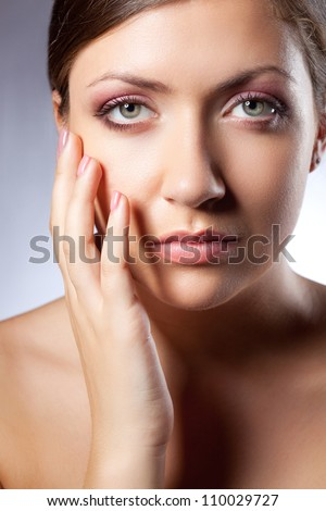 beautiful woman face portrait with hand over blue looking at camera - stock photo