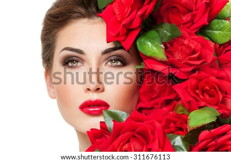 Beautiful woman face surrounded by red roses. Perfect skin. Professional makeup. - stock photo
