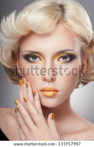 Beautiful woman face with luxury gold makeup - stock photo