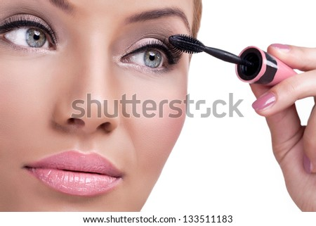 Beautiful woman face with mascara brush - stock photo