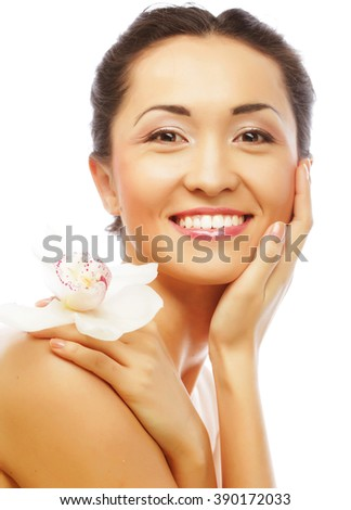 Beautiful woman face with orchid flower - stock photo