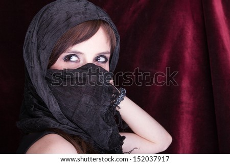 Beautiful Woman Face with scarf closeup black background - stock photo