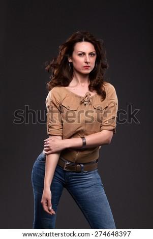Beautiful woman fashion model wearing jeans and posing in studio. - stock photo