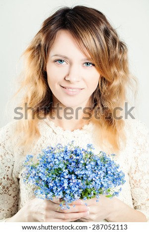 Beautiful Woman Fashion Model with Blue forget-me-not Flowers  - stock photo