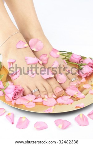 Beautiful woman  feet with flowers and  rose petals over white - stock photo
