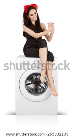 Beautiful Woman Filing her Nails on a Washing Machine - Young bored housewife spending time doing her manicure on a washer  - stock photo