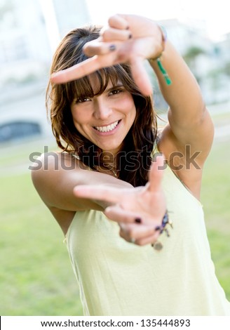Beautiful woman framing her face with fingers - stock photo