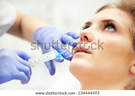 Beautiful woman gets an injection in her lips - stock photo