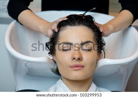 Beautiful woman getting a hair wash. In a hair salon - stock photo