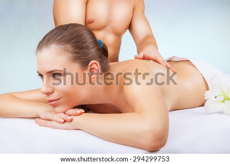 Beautiful woman getting a massage on a light background - stock photo