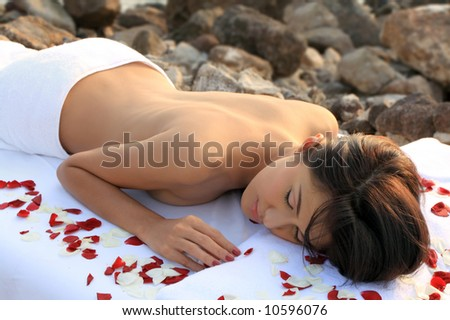 Beautiful woman getting massage & spa treatment in natural setting. - stock photo