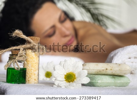 Beautiful Woman Getting Spa Massage in Spa Salon. Focus on the flower. - stock photo