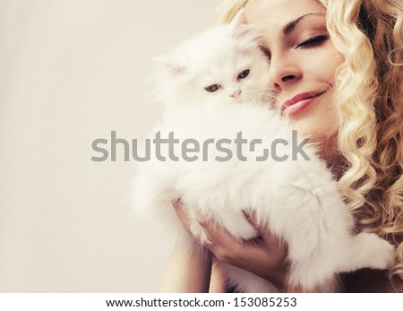 Beautiful woman golding fluffy white Persian kitten - stock photo