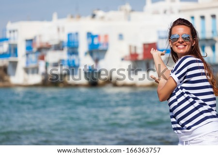 Beautiful woman greeting, smiling and looking at camera beside the sea - stock photo