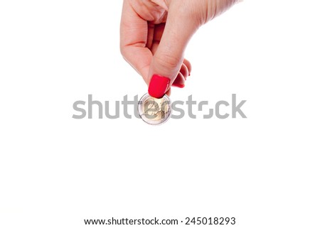 Beautiful woman hand with manicure holding euro coin - stock photo