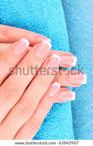 Beautiful woman hands with french manicure on blue background - stock photo