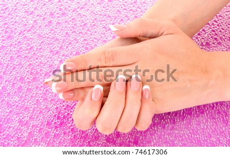 Beautiful woman hands with french manicure on pink background - stock photo