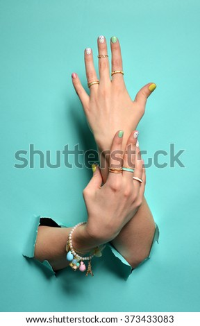 Beautiful woman hands with yellow pink white pattern nail polish and silver stacking rings and bracelets on a mint background - stock photo