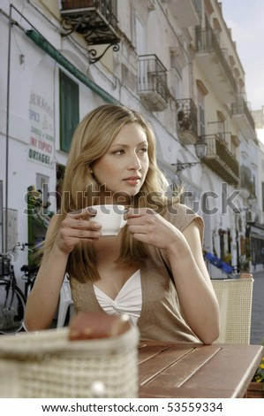 Beautiful woman having a cup of cappuccino - stock photo