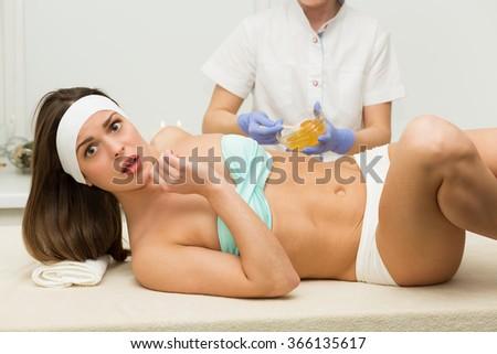 Beautiful woman having a sugaring depilation beauty treatment - stock photo