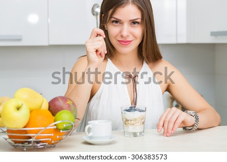 Beautiful woman having coffee, fruits and oatmeal for breakfast - stock photo