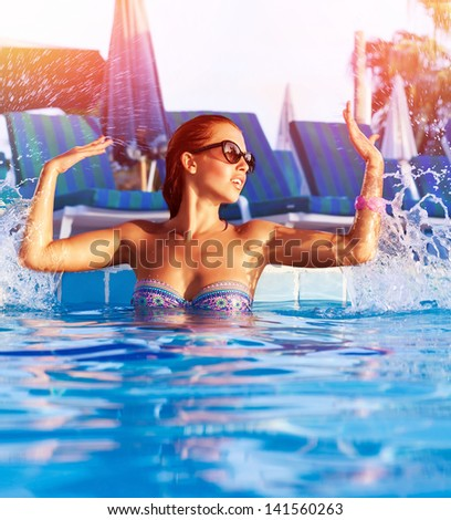 Beautiful woman having fun in the pool, making water splash by hands, enjoying hot summer day in swimming-pool, summertime holiday and vacation, refreshment concept  - stock photo